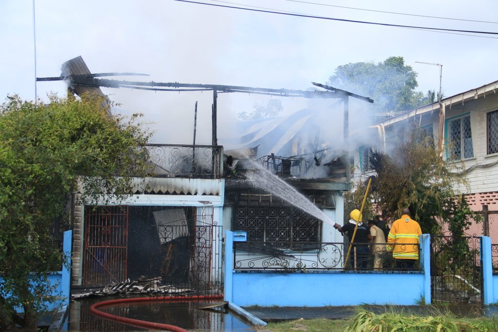 Firefighters battling to douse the blaze, which engulfed the South Ruimveldt home